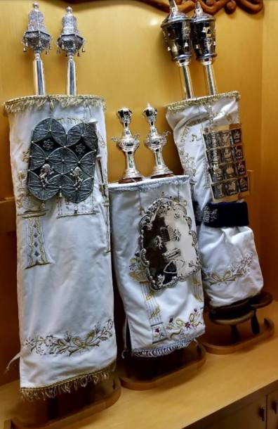 """Peninsula Sinai Congregation's scroll from České Budějovice (MST #685, left), dressed in its beautiful High Holiday finery. Peninsula Sinai's """"Olomouc Scroll"""" (MST #740, right) was returned to Olomouc in October, 2017 at the behest of the Memorial Scrolls Trust and in partnership with the Olomouc community and Peninsula Sinai Congregation. The scroll had a blue band around the outside when this picture was taken, shortly before the High Holidays, indicating it was """"passul"""" or ritually unfit. Through the efforts of Sofer Rabbi Moshe Druin and his """"Sofer on Site"""" team, the scroll was completely repaired and rendered Kosher for ritual use in a ceremony in Olomouc in October, 2017 witnessed by hundreds of community members and witnesses from overseas."""