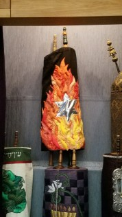 Temple Israel, Dayton, OH's České Budějovice scroll (MST #313) . Temple Israel's Conformation Class commissioned the cover with a star on a black background which is unconsumed by the flames surrounding it. The cover was handmade by Temple Israel President, Carol Finley.